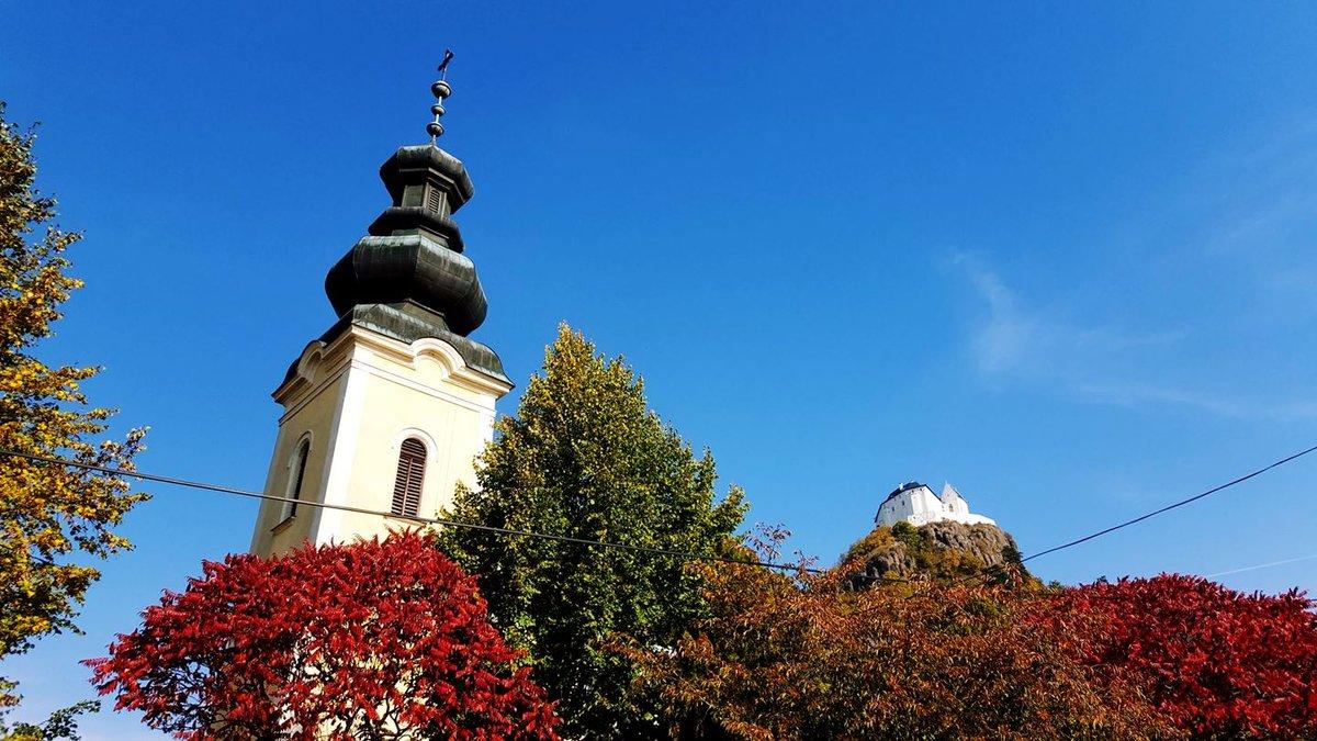 A Szent István Római katolikus templom tornya és a Füzéri vár a háttérben