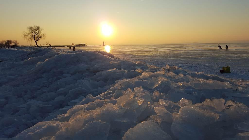 A befagyott tó felett nemsokára lemegy a nap.